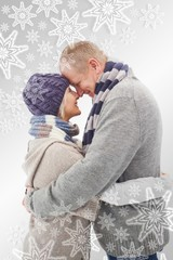 Composite image of happy mature couple in winter clothes hugging