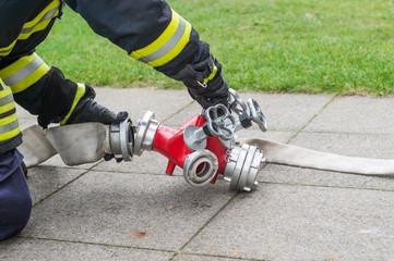Feuerwehrmann schließt Schlauch an Verteiler an