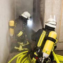 Feuerwehrmänner dringen in brennendes Gebäude vor