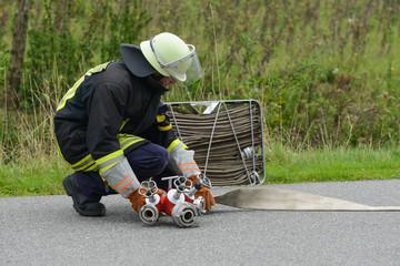 Feuerwehrmann baut Wasserversorgung auf