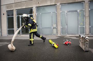 Feuerwehrmann rollt Schlauch zum Löschen aus