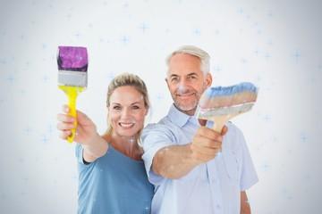 Happy couple holding paintbrushes smiling at camera