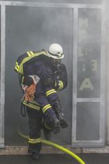 Feuerwehrmann rettet Person aus brennendem Gebäude