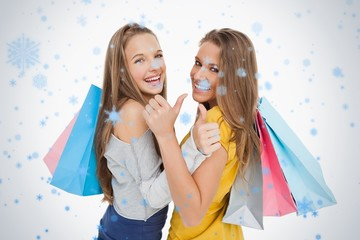 Rear view of two young women the thumbup with shopping bags