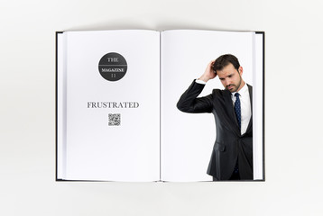 Young business man hearing something printed on book