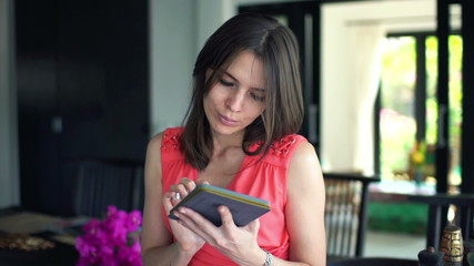 Young woman reading book on ebook reader at home