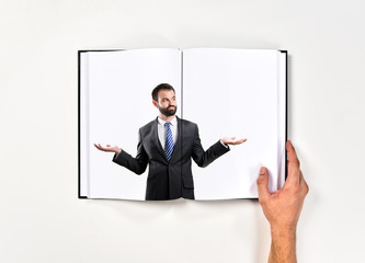 Businessman making a balance gesture printed on book