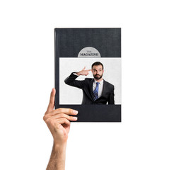 Young businessman committing suicide printed on book