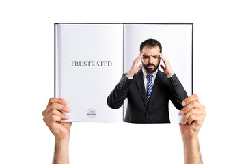 Young businessman with headache printed on book