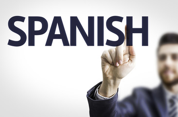 Business man pointing to transparent board with text: Spanish