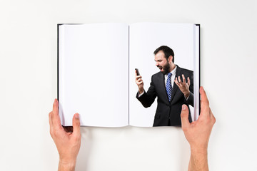 Young businessmen shouting to mobile printed on book