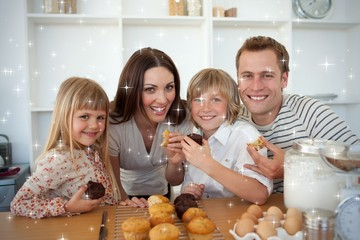 Cute children eating muffins with their parents