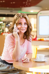 beautiful girl calling by phone in cafe market