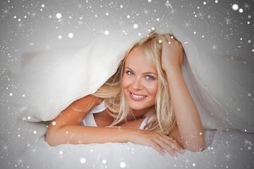 Composite image of smiling woman under a duvet