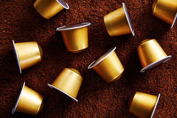 Gold coffee capsules on coffee background