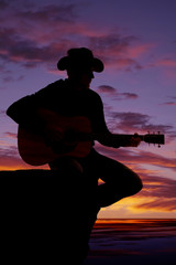 silhouette of man with guitar sit by water sunset