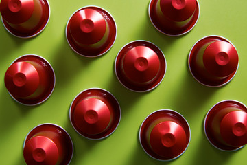 Red coffee capsules on green background