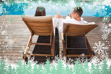 Couple toasting champagne by swimming pool
