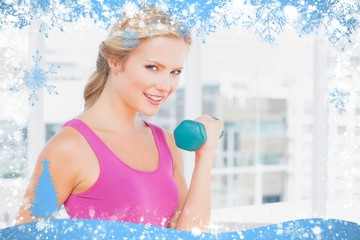 Pretty blonde lifting dumbbells and smiling at camera