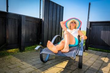 Frau auf der Terrasse im Urlaub