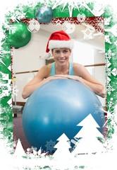 Fit smiling brunette in santa hat leaning on exercise ball