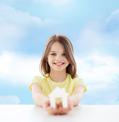 beautiful little girl holding paper house cutout