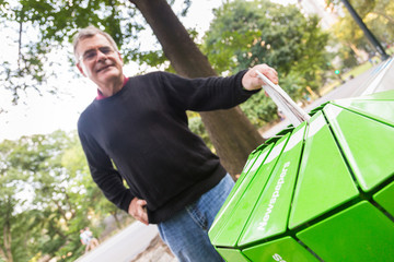 Senior Man Wasting Newspaper in Recycling Basket