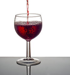 Red wine pouring into glass.