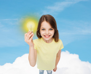 smiling little girl holding light bulb