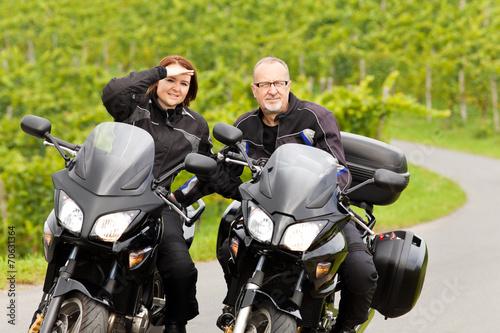 canvas print picture Zweiradfahrer mit Blick in die Kamera auf ihren Motorrädern