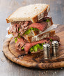 Roast beef sandwiches with lettuce on wooden cutting board on da