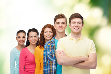 group of smiling teenagers over green background