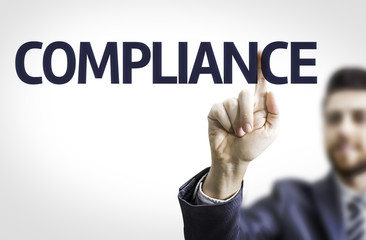 Business man pointing to transparent board with text: Compliance