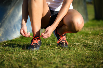 Female runner lacing sport and running shoes