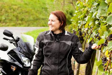 Motorradfahrerin pflückt Weintrauben