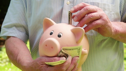 Man putting money into a piggy bank for saving