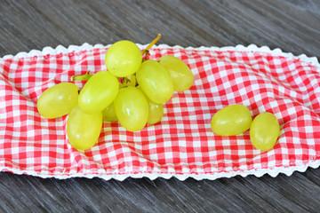 tros groene druiven op een geruit kleedje