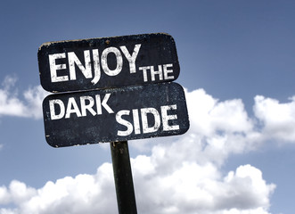 Enjoy The Dark Side sign with clouds and sky background