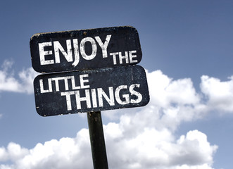Enjoy The Little Things sign with clouds and sky background