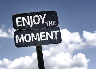Enjoy The Moment sign with clouds and sky background