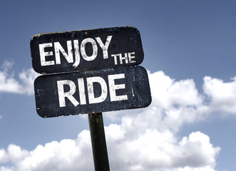 Enjoy The Ride sign with clouds and sky background