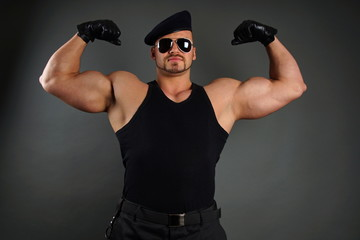 Muscular soldier poses and shows his biceps