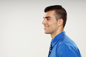 Profile of smiling young man in blue shirt