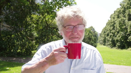 Friendly Older Man with Coffee mug in his hand in Park
