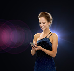 smiling woman in evening dress with smartphone