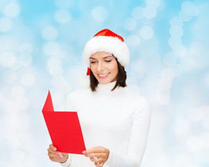 smiling woman in santa hat with greeting card