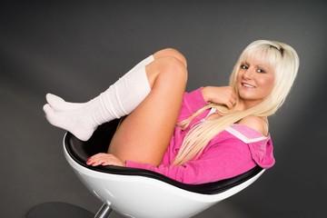 blonde Frau sitzt in einem Stuhl