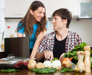 Smiling couple cooking with notebook
