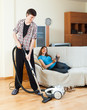 man cleaning with vacuum cleaner while wife lying with eBook