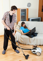 Guy doing house cleaning during girl resting
